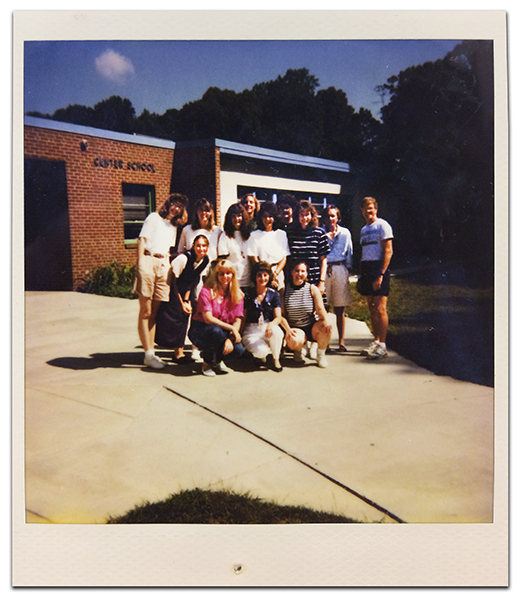 Color Polaroid photograph of North Springfield Center staff taken during the 1993 to 1994 school year. 13 adults are standing on the sidewalk in front of the building. Lettering on the wall near the entryway reads: Center School.