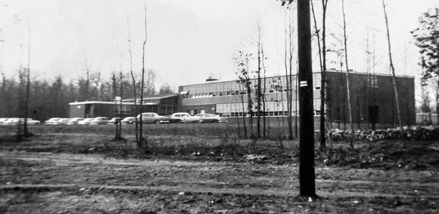 Black and white photograph of North Springfield Elementary School taken in 1958 for a fire insurance survey for the Fairfax County School Board. The school is seen from Heming Avenue and because there are so few trees at this time the rear of the building is visible. A two-story classroom wing and the cafeteria are visible from this angle. There is a row of 1950s era cars parked outside.