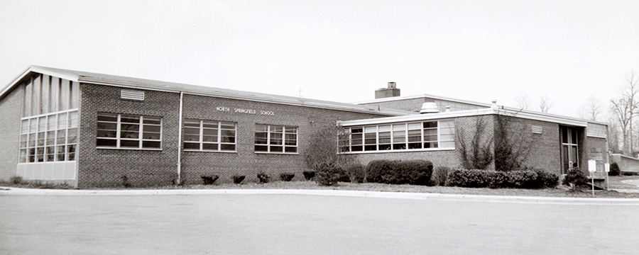 Black and white photograph of the front of North Springfield Elementary School taken in the 1960s. It appears to pre-date the color photograph shown later on this page because the shrubs in front of the building are smaller in size.