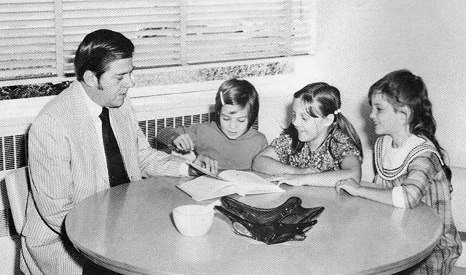 Black and white yearbook photograph of Principal Ronald E. West. He is seated at a table looking at a book with three students.